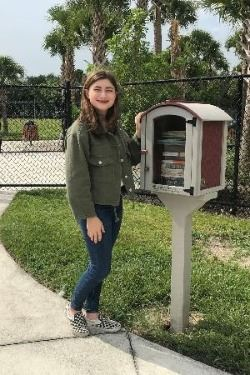 Picture of Grace standing by the Little Free Library she donated at Cinquez Park.